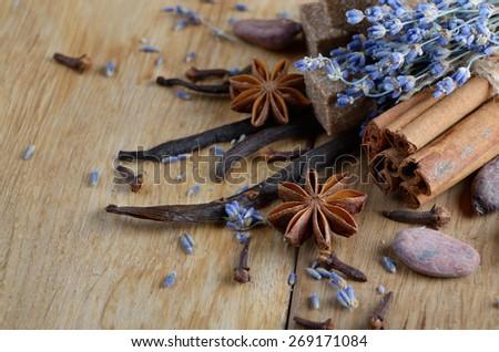 Vanilla, cinnamon, cocoa, anise and cloves on wooden table - stock photo