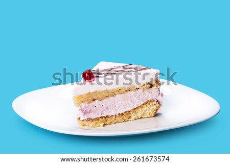 vanilla cream piece of cake on a blue background - stock photo