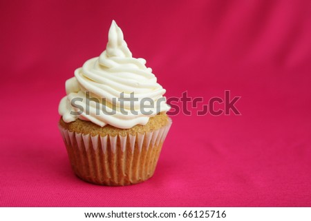 Vanilla cup cake with white icing on red background - stock photo