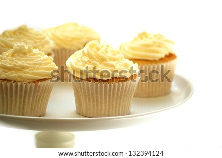 vanilla cup cakes on cake stand on white - stock photo
