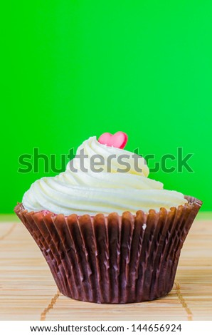 Vanilla cupcake on the table with colorful background - stock photo