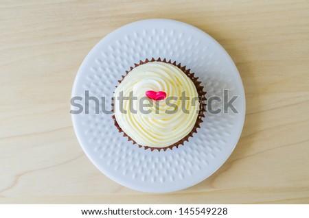 Vanilla cupcake on the wood table - stock photo
