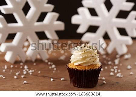 Vanilla cupcake on white snow flakes Christmas background - stock photo