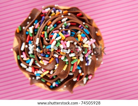 Vanilla Cupcake with Chocolate Frosting Covered in Sprinkles on Striped Pink Background - stock photo