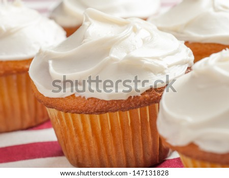 Vanilla cupcakes on a red and white tablecloth. - stock photo