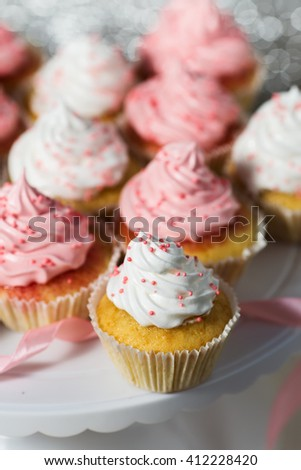 Vanilla cupcakes with pink and white cream, selective focus, close up - stock photo