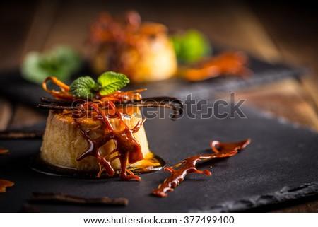 Vanilla flan dessert served on black slate - stock photo