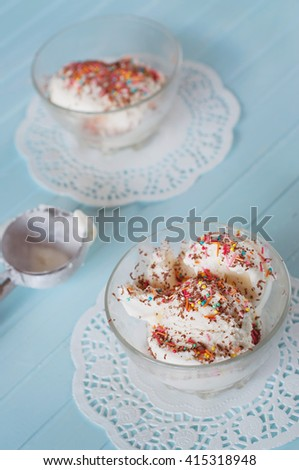 Vanilla ice cream in bowls sprinkled with chocolate and multicolored sprinkles - stock photo