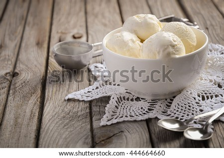 Vanilla ice cream in white bowl on rustic wooden background, selective focus, copy space - stock photo
