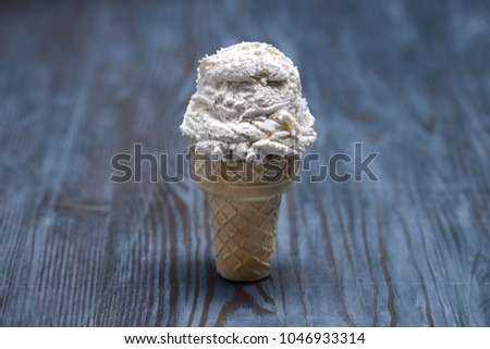 Vanilla ice cream scoop with cone on wooden background