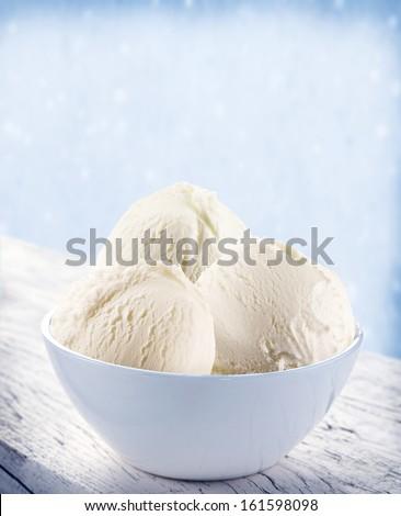Vanilla ice-cream scoops in white cup over snow background. - stock photo