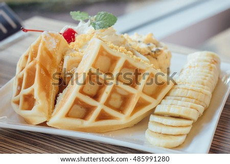 vanilla ice cream sundae with waffle and banana in white dish on table