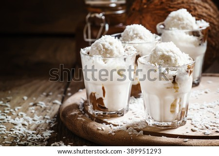Vanilla ice cream with coconut and caramel sauce, selective focus
