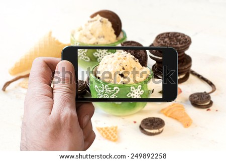 Vanilla ice cream with cookies in the cups photographing by camera of mobile phone ,selective focus  - stock photo