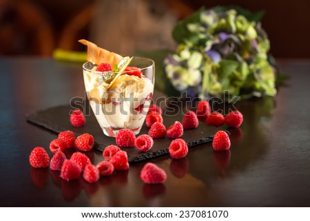 Vanilla ice cream with raspberry and flowers on wooden table - stock photo
