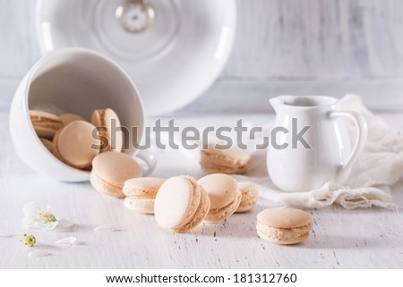 Vanilla macarons with apple flowers on white wooden table
