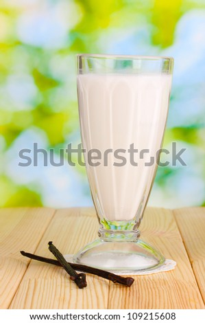Vanilla milk shake on wooden table on bright background