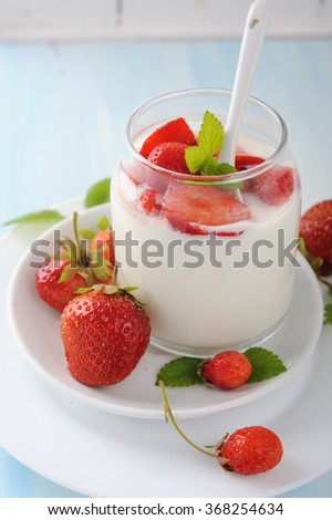 Vanilla panna cotta with fresh strawberry in glass jar