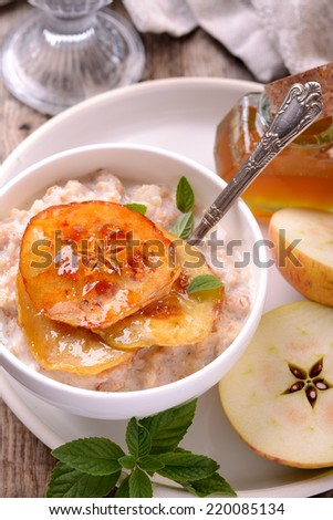 vanilla porridge of oatmeal with honey caramel apples slices with mint leaves and natural vanilla pod on a wooden table with vintage teaspoons - stock photo