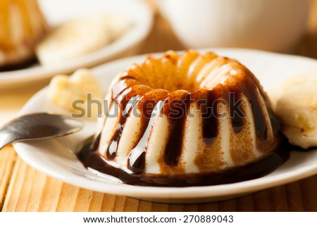 Vanilla pudding with choccolate syrup and banana slices served on white plate
