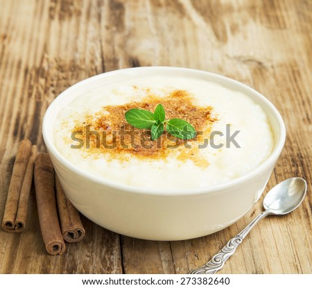 Vanilla Rice Pudding with Cinnamon Powder and Mint Leaf, Delicious Dessert - stock photo