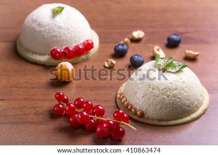 Vanilla souffle and berries on wooden background - stock photo