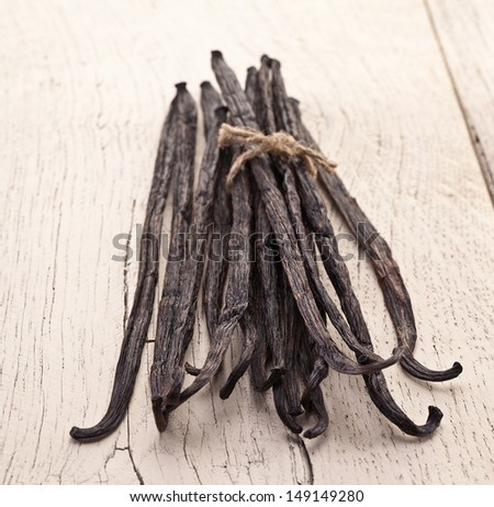 Vanilla sticks on a white wooden table. - stock photo