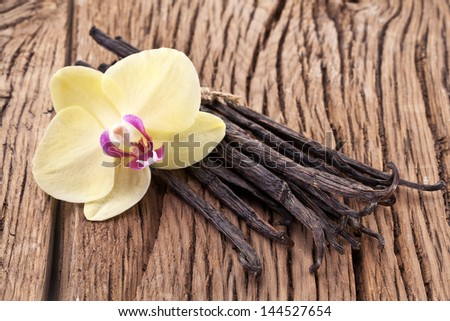 Vanilla sticks with a flower on a wooden table. - stock photo