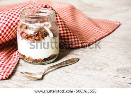 Vanilla yogurt dessert with chocolate cookies and fresh cherry in a jar on a wooden table, selective focus
