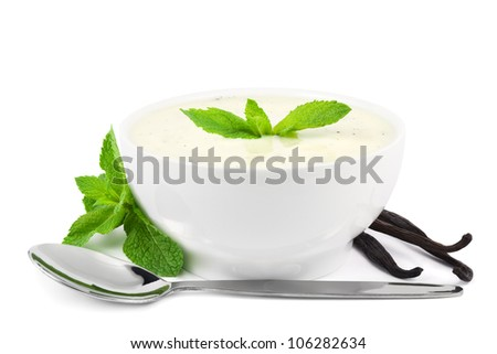 Vanilla yogurt with mint leaves, vanilla pods, and a spoon on white - stock photo