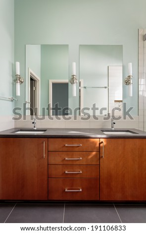 Vanity double sink and mirrors in modern bathroom/Vertical shot of a custom master bathroom vanity