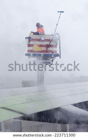 VANTAA AIRPORT, HELSINKI, FINLAND - CIRCA APRIL, 2013: Process of aircraft wings deicing with antifreeze before takeoff during strong blizzard. Services of large Finland airport - stock photo