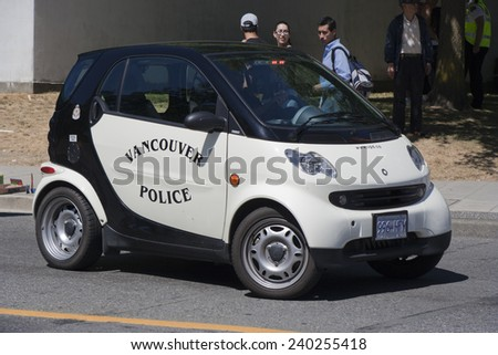 VANVOUVER, CANADA - AUGUST 6, 2005: Canadian Police car parking in front of tourists. The Police car is a two-seater car Smart, a fuel efficient compact car built by Daimler Benz. - stock photo