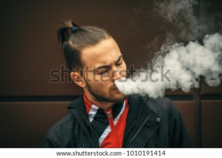 Vape man. Portrait of a handsome young white guy with modern haircut in red sport jacket vaping an electronic cigarette opposite the futuristic urban