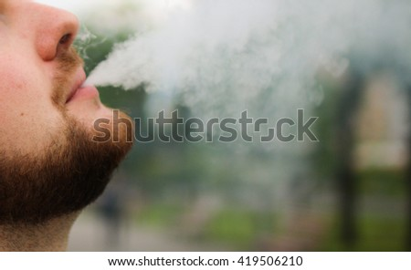 Vaping bearded man. The bearded man smoking electronic cigarette on the street.  - stock photo
