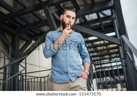 Vaping. Men with beard vaping electronic cigarette outdoor.
