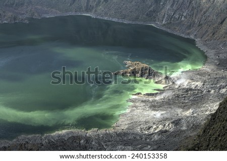Vapor and gas vents and green colored water in interior of active barren volcanic crater El Chichonal in Chiapas, Mexico on December 19, 2014 - stock photo