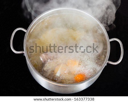 vapor over boiling of beef broth in pan on glass ceramic cooker - stock photo