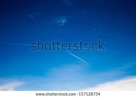 Vapor trail from an airplane in the blue sky, the moon and the plane - stock photo