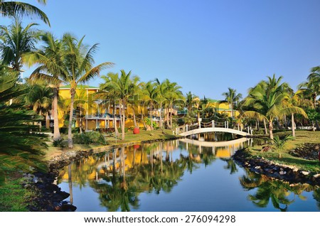 Varadero, Cuba - April 30, 2014. Bungalows of hotel in territory with palm trees, river and a bridge. - stock photo