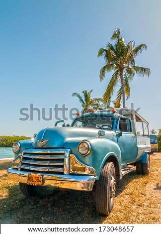 VARADERO, CUBA - APRIL 24: Old american car standing under palm tree backlighted by sun shown on 24 April 2008 in Varadero, Cuba