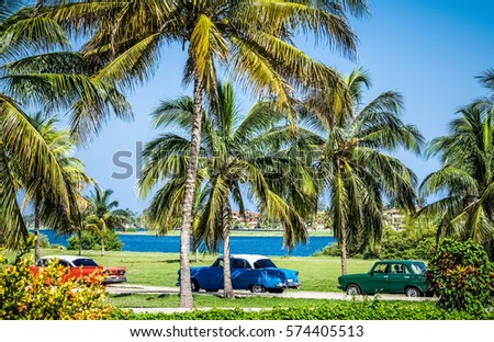 Varadero, Cuba - June 17, 2015: HDR - Many american Chevrolet classic cars with white roof parking in Varadero Cuba under palms near the beach - Serie Cuba Reportage