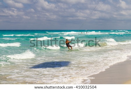 Varadero, Cuba - March 6, 2016: Young athletic male surfing on waves in Varadero under a kite - stock photo