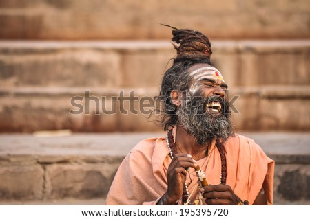 Varanasi, India - April 19, 2010: Happy Guru Laughing in joy at Ganga river. The most holy river of India and Hindu culture. - stock photo