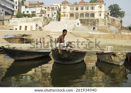 VARANASI, INDIA - APRIL 30: Unidentified Indian man goes fishing in the Ganges River on April 30, 2009 in Varanasi, India. For most of Varanasi's dwellers fish is important source of livelihood. - stock photo