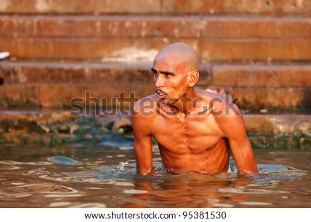 VARANASI, INDIA - APRIL 24: Unidentified man taking ritual bath in the river Ganga on April 24, 2011 in the holy city of Varanasi, India. The holy ritual bath is held every day.