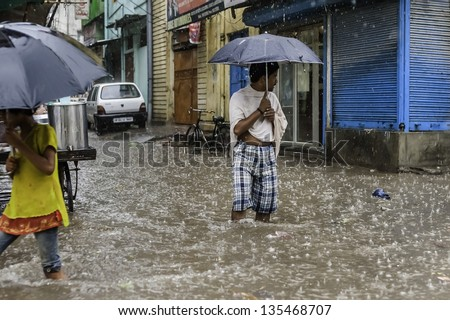 VARANASI, INDIA - AUGUST 11: Heavy monsoon rain causes a flash flood and this man finds himself momentarily stranded on August 11, 2011 in Varanasi, India.