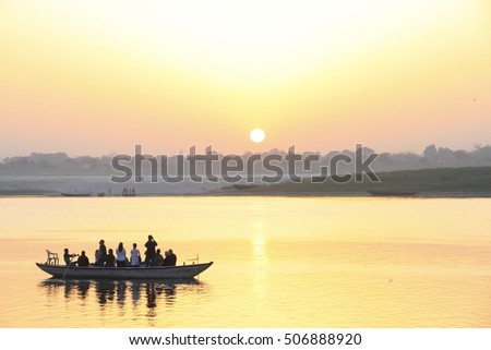 VARANASI INDIA - CIRCA 2012 - Unidentified pilgrims take to the holy River Ganges at sunrise for the early morning Puja ceremony and bathing from the Ghats.