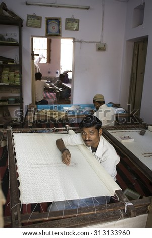 VARANASI, INDIA DEC, 2013: Unidentified Indian man embroidering a traditional sari cloth, on old fabric factory on Dec, 2013, Varanasi, India. Textile industry in Varanasi preserved ancient traditions - stock photo