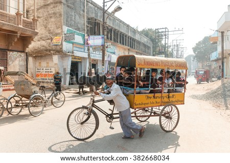 VARANASI, INDIA - DECEMBER 1: Unidentified Cycle rickshaw carries unidentified children to school on December 1, 2012 in Varanasi. Cycle rickshaws are widely used in cities of India. - stock photo